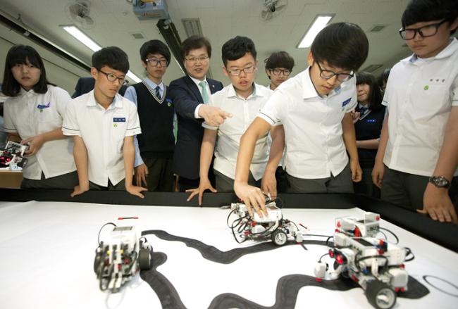 미래창조과학부 최양희 장관이 지난 5월 인천의 한 중학교를 찾아 학생들과 소프트웨어(SW)교육에 참여하고 있는 모습.