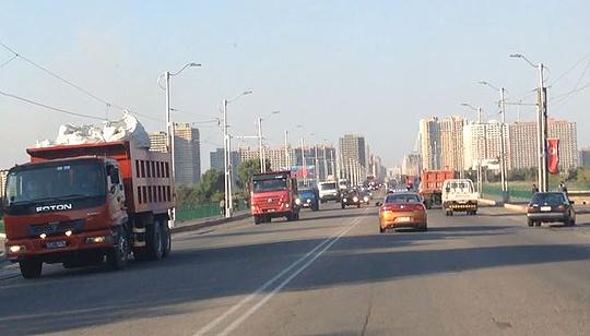 평양시내로 들어가는 도로에 각종 차량들이 오가고 있다. 도로 오른편에 걸려있는 인공기가 흔들리고 있다. 제보 영상 캡처. ⓒ데일리안