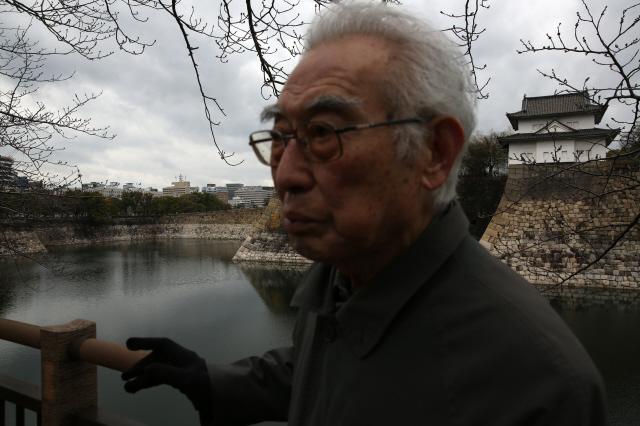 <화산도/> 김석범 작가가 일본 오사카 오테마에공원에서 1948년 4월 조선학교 폐쇄 항의 시위를 회고하고 있다. 뒤쪽으로 시위 당시 그가 지사 면담을 요구하며 진입을 시도했던 오사카부청(왼쪽 일장기가 보이는 건물)과 오사카성(오른쪽)이 보인다.