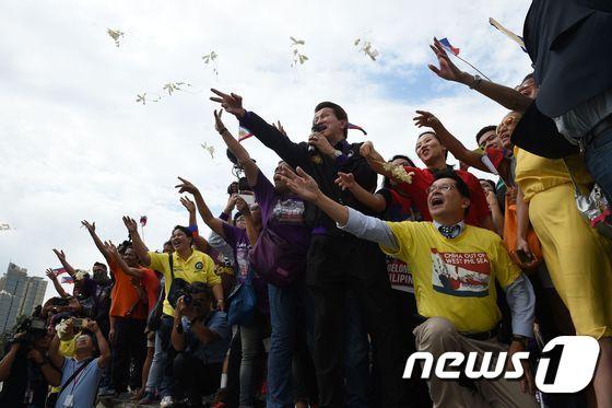 필리핀과 베트남 시민운동가들이 12일(현지시간) 마닐라에서 헤이그 상설중재재판소의 판결을 기다리며 염원을 담은 꽃을 날리고 있다.   © AFP=뉴스1