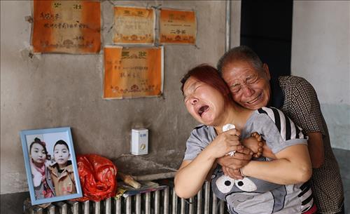 중국 허베이성 징싱현을 덮친 폭우로 자식을 잃은 여성이 오열을 하고 있다. 징싱현에서만 36명이 사망했고 35명의 생사가 여전히 확인되지 않다.[봉황망 캡처]
