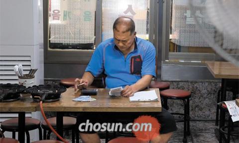 시름 깊어지는 자영업자 - 최저 시급 인상은 서민들의 삶에 빛과 그림자를 만들었다. 저임금에 시달리던 비정규직은 임금 인상을 반기지만 고용이 줄지 않을까 걱정이다. 자영업자들은 당장 직원들 월급 올려줄 걱정에 한숨이 깊다. 17일 오후 서울 종로3가 한 백반집 사장이 점심때가 지난 텅 빈 식당에 앉아 계산기를 두드리며 중간 결산을 하고 있다. /오종찬 기자