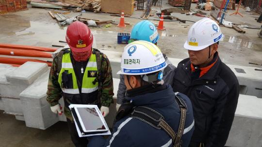 지난 2014년 삼성물산이 도입한 현장업무 모바일 시스템 '스마트 어플리케이션 위(WE)'를 홯용해 시공 관리자들이 업무 협의를 하고 있다.  /사진제공=삼성물산