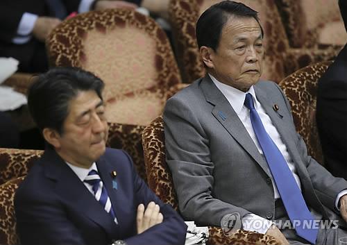 아베 신조(왼쪽) 일본 총리가 19일(현지시간) 도쿄 의사당에서 열린 참의원 예산위원회에 출석, 팔짱을 낀 채 아소 다로 부총리 겸 재무상 옆에 나란히 앉아 있다. [EPA=연합뉴스 자료사진]