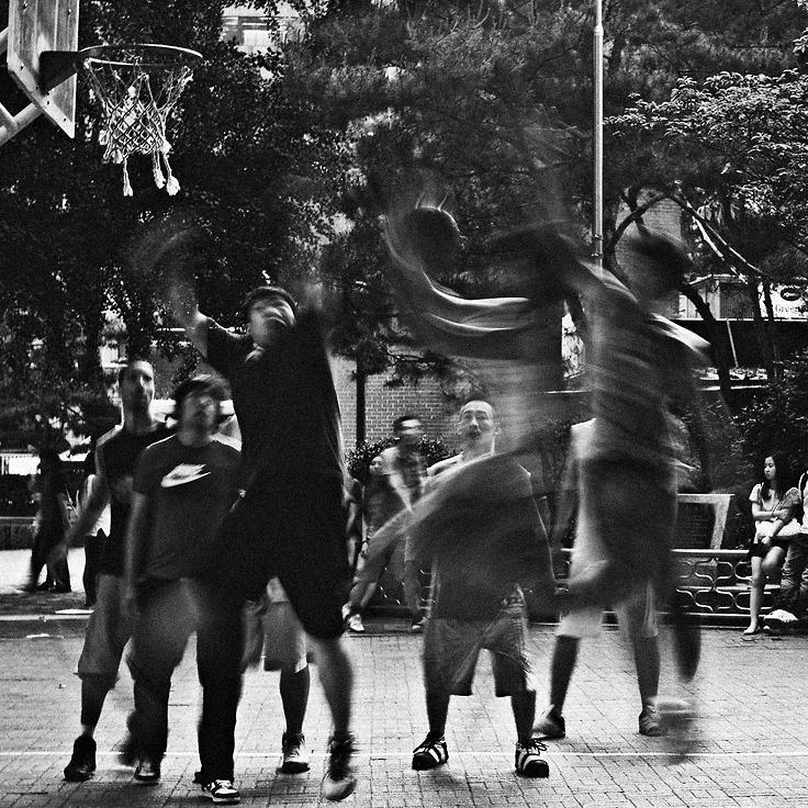 레이업슛을 넣으려 점프한 공격수와 막으려 블러킹하는 두명의 수비수들