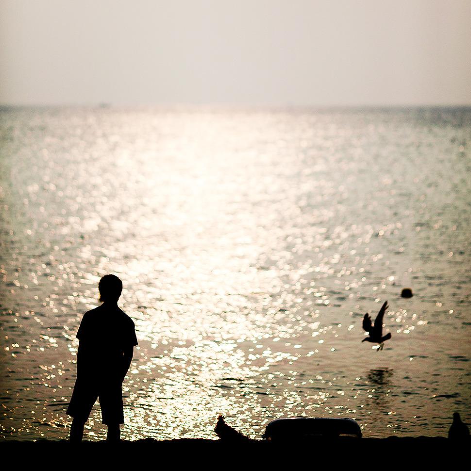 한명의 남자가 바다를 바라보고 서있고 역광으로 촬영되어 실루엣만 보이는 사진.