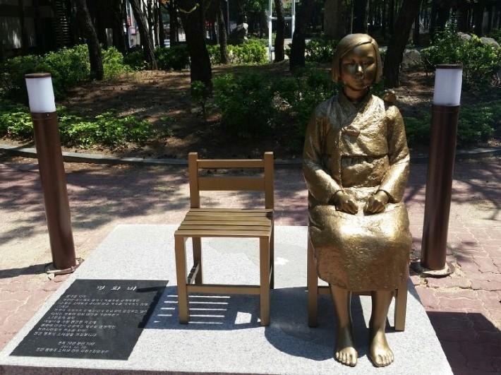 사진: 전국에 있는 위안부 소녀상 중 하나. 쓸쓸한 빈 의자를 곁에 두고 있다. [위안부 소녀상 철거 - 한일 위안부 합의와 한일 협정]