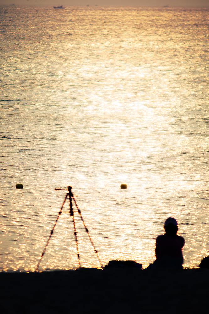 해변에 노을이 떨어지고 삼각대와 사람의 실루엣이 흐릿하게 보이는 사진.