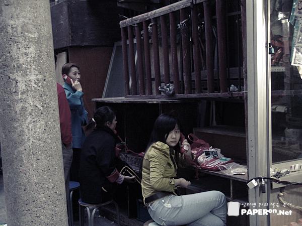 골목길 안쪽에 위치한 시외전용 전화를 이용하는 베이징 시민들