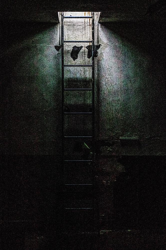 깜깜한 공간에 윗층으로 올라가는 사다리가 있고 약간의 공간에 빛이 새어 들어오고있는 사진