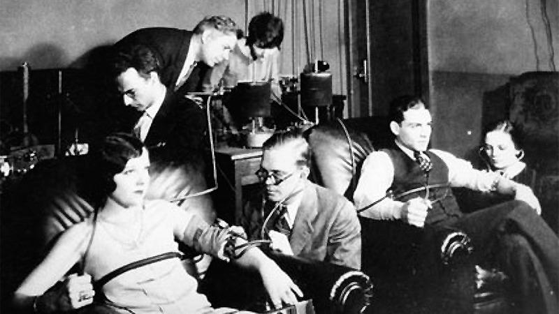사진: 최초의 거짓말 탐지기 발명가 윌리엄 몰튼 마스턴이 시연을 보이고 있다. 기계를 보고 있는 뒤쪽 가운데가 머스턴. [페미니즘 원더우먼 비하인드 스토리]