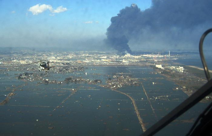 사진: 쓰나미가 덮친 일본 도호쿠 대지진 당시의 모습. 구조 헬기에서 불타는 현장을 찍었다. 이 피해로 1만 8천명 이상의 사상자가 발생하였다. 그후 후쿠시마 원전의 사고도 터졌다. [동일본대지진의 엔도 미키]