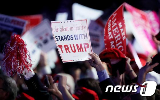 도널드 트럼프 미국 대통령 당선인의 지지자들이 선거 당일 '조용한 다수가 트럼프를 지지한다'는 구호를 들고 있다. © AFP=뉴스1
