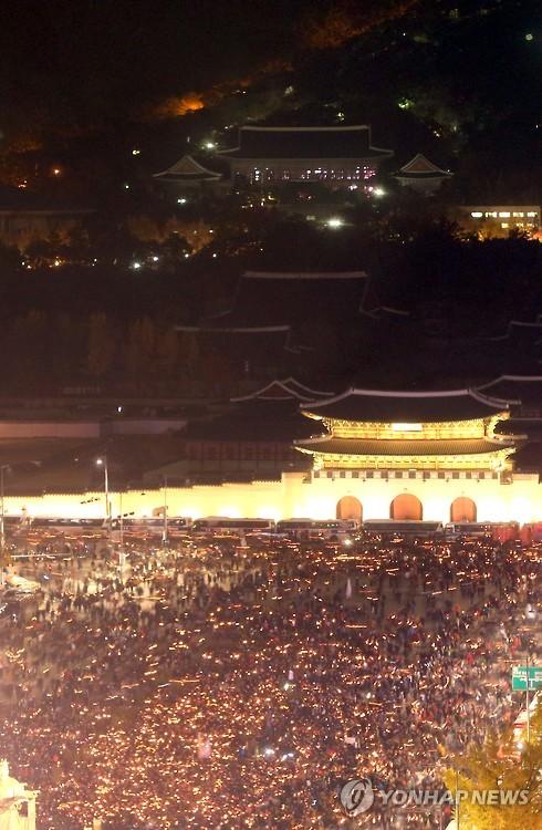 불 밝힌 촛불, 불 켜진 청와대      (서울 사진공동취재단=연합뉴스) 박근혜 대통령 퇴진을 요구하는 민중총궐기 대회가 열린 12일 오후 대회에 참가한 시민들이 서울 광화문광장을 가득 메우고 촛불을 밝히고 있다. 뒷편으로 불 켜진 청와대가 보인다.