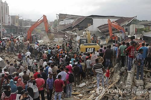 '잔해 속 사람들 다치지 않게…'        (피디에 자야<인도네시아> AP=연합뉴스) 인도네시아 서부 아체주 해안에서 7일 오전(현지시간) 발생한 규모 6.5의 강진으로 8일 오전 현재 99명이 숨지고 136명이 중상인 것으로 집계됐다.       사진은 피디에 지야에서 7일 건물 잔해 속에 묻힌 피해자 구조에 포크레인이 동원된 모습.