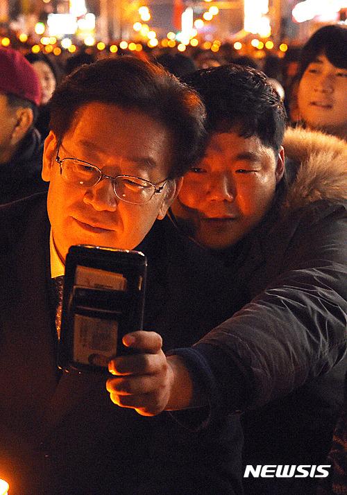 """【대전=뉴시스】함형서 기자= 17일 오후 대전 서구 둔산동 갤러리아 타임월드 앞에서 열린 """"박근혜 대통령 퇴진 5차 시국대회에서 이재명 성남시장이 한 시민과 사진을 찍고 있다. 2016.12.17.  foodwork23@newsis.com"""