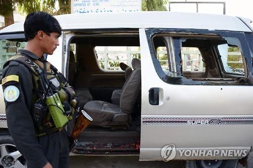 17일 아프가니스탄 남부 칸다하르에서 무장괴한의 총격으로 여성 공항 보안직원 5명과 운전사 등 6명이 사망했다. 한 경찰관이 총격을 받은 승합차를 살펴보고 있다.[AFP=연합뉴스]