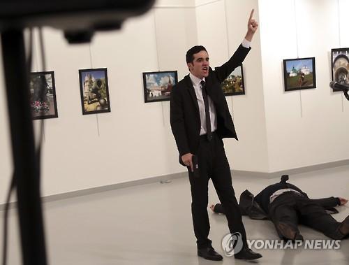19일 터키 수도 앙카라의 한 전시회에서 안드레이 카를로프 주터리 러시아대사가 괴한의 총격으로 숨졌다. 사진은 총격범이 사건 직후 소리를 지르며 연설하는 모습. [AP=연합뉴스]