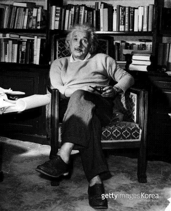 알베르트 아인슈타인이 1934년 파이프 담배를 손에 들고 의자에 앉아 있다. Photo by Lucien Aigner/Three Lions/Hulton Archive/Getty Images