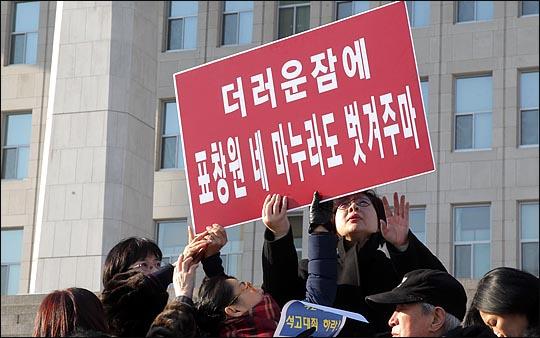 새누리당 전국여성의원협의회 소속 회원들이 25일 오후 국회 본청 앞 계단에서 박근혜 대통령이 묘사된 풍자 누드화 '더러운잠'이 전시된 풍자전시회로 논란을 빚은 표창원 의원의 사퇴를 요구하며 '더러운잠에 표창원 네 마누라도 벗겨주마'라고 씌여진 피켓을 들고 있다. ⓒ데일리안 박항구 기자