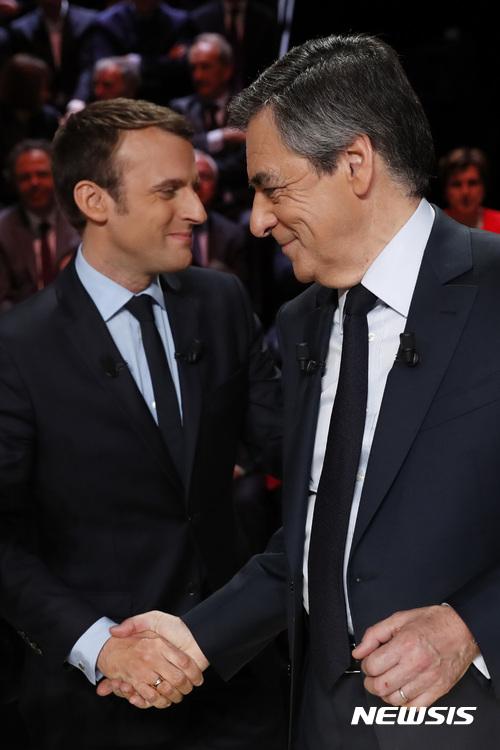 【오베르빌리=AP/뉴시스】프랑스 무소속 대선 후보 에마뉘엘 마크롱(왼쪽) 전 경제장관과 보수당 후보 프랑수아 피용 전 총리가 20일(현지시간) 1차 대선 TV 토론 전 악수를 하고 있다. 2017.3.21.