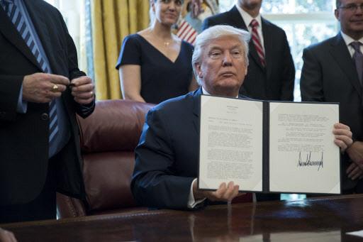 도널드 트럼프 미국 대통령이 20일(현지시간) 백악관에서 미 철강업계 CEO들이 참석한 가운데 철강 수입에 대해 무역확장법 232조를 발령하는 내용의 행정각서에 서명한 뒤 이를 들어보이고 있다. 연합뉴스