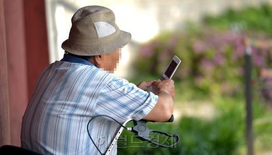 한 노인이 홀로 핸드폰을 만지고 있다. [사진=헤럴드경제DB]