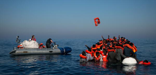 반쯤 가라앉고 있는 난민보트에 시와치 구조대원이 접근하고 있다.