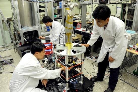 표준과학연구원 연구자들이 세슘 원자시계를 살펴보고 있다./표준연 제공