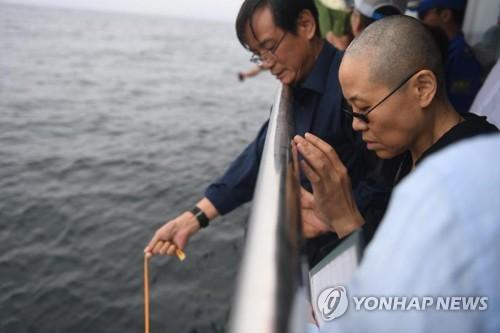 지난 15일 노벨평화상 수상자인 중국 인권운동가 류샤오보의 시신이 화장된 뒤 랴오닝성 다롄 앞 바다에 해장(海葬)됐다. 류샤오보 동생 류샤오쉬안(오른쪽 2번째)이 유골함을 바다에 내리는 모습을 아내 류샤가 바라보고 있다.