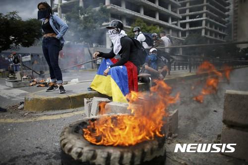 【카라카스(베네수엘라)=AP/뉴시스】니콜라스 마두로 베네수엘라 대통령 에 반대하는 시위대가 4일 수도 카라카스에서 타이어에 불을 붙여 바리케이드를 설치한 채 제헌의회 출범에 항의하고 있다. 베네수엘라군은 4일 마두로 대통령을 강력하게 비난해온 루이사 오르테가 검찰총장의 사무실을 포위, 오르테가 해임이 임박했음을 알렸다. 2017.8.5