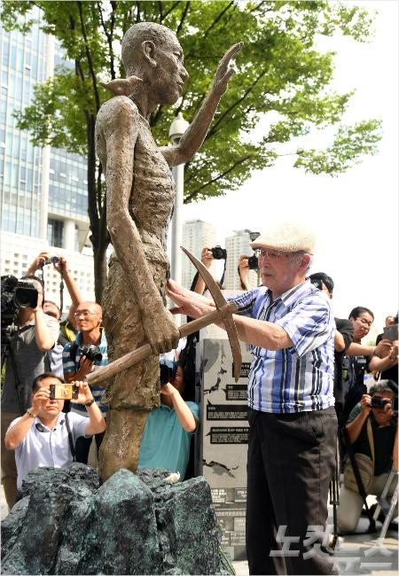 12일 오후 서울 용산역 광장에서 열린 '강제징용 노동자상 건립 제막식' 에 참석한 강제징용 피해자 김한수 할아버지가 노동자상을 어루만지고 있다. (사진=황진환 기자)