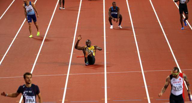 우사인 볼트(가운데)가 13일 런던 세계선수권 남자 400m 계주 결선에서 마지막 주자로 나서 허벅지 부상으로 쓰러져 있다. 런던=EPA 연합뉴스