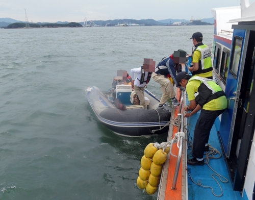 13일 오전 10시 15분께 충남 태안군 영목항 북동쪽 5㎞ 해상에서 레저 보트가 표류해 신고를 받고 출동한 해경이 탑승자들을 구조하고 있다. 2017.8.13 [태안해경 제공=연합뉴스]