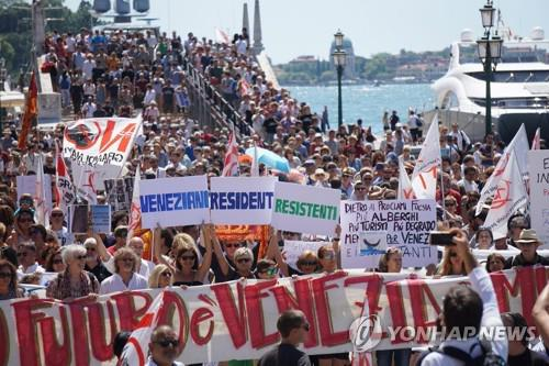 지난 7월 2일 이탈리아 베네치아에서 주민들이 '베네치아 주민들은 저항한다'라는 현수막을 들고 몰려드는 관광객으로 주민들의 이탈이 가속화하고 있는 상황에 항의하고 있다. [EPA=연합뉴스 자료사진]