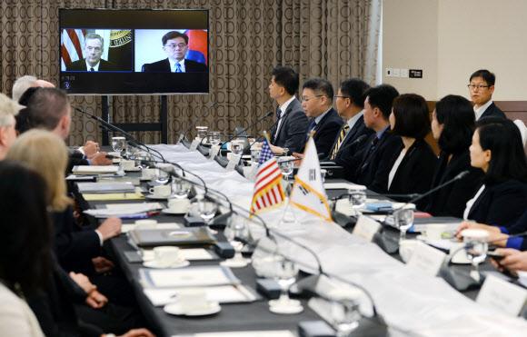 김현종(영상 오른쪽) 산업통상자원부 통상교섭본부장과 로버트 라이트하이저 미국 무역대표부 대표 등 한·미 FTA 대표 협상단이 22일 서울 중구 롯데호텔에서 영상회의를 열고 있다.산업통상자원부 제공