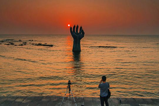 경북 포항시 남구 호미곶을 찾은 여행객이 갈매기들이 앉아 쉬는 '상생의 손' 너머로 붉게 솟아오르는 해를 카메라에 담고 있다.