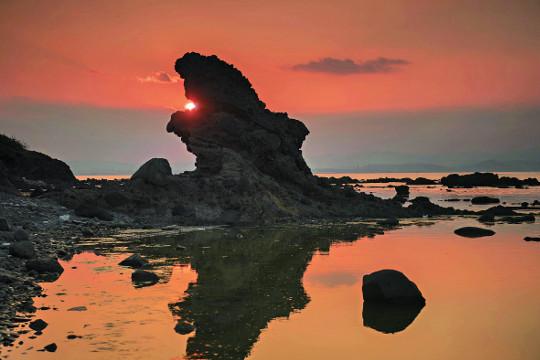 석양이 아름다운 호미곶 까꾸리계 앞바다에 웅크리고 앉아 바다를 굽어보는 모습의 독수리 바위가 해를 삼키고 하늘로 비상할 것처럼 보인다.