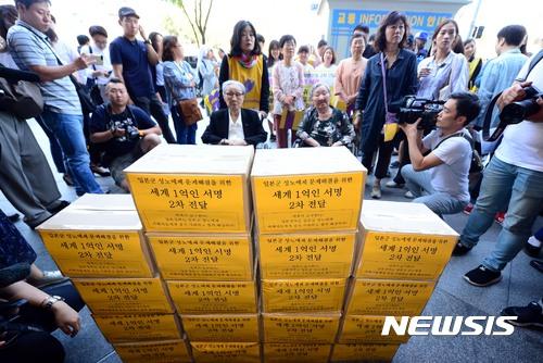 【서울=뉴시스】조성봉 기자 = 일본군 '위안부' 피해자 김복동, 길원옥 할머니를 비롯한 1300차 수요시위 참가자들이 13일 오전 서울 종로구 주한일본대사관에 일본군성노예제 문제해결을 위한 세계 1억인 서명지를 전달하고 있다. 이날 주한일본대사관 관계자가 서명지를 전달받을 예정이었으나, 대사관 보안 관계자들이 서명지를 옮겼다. 2017.09.13.suncho21@newsis.com