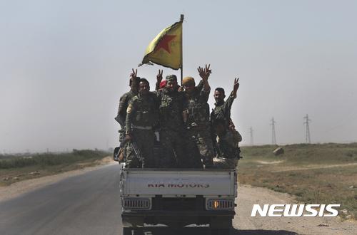 【락까=AP/뉴시스】극단이슬람 무장조직 이슬람국가(IS)의 수도 격인 락까로 연결되는 도로에서 26일(현지시간) 미군의 지원을 받는 시리아자유군(SDF) 군인들이 트럭을 타고 이동하는 동안 손가락으로 승리의 브이(V)자를 만들어 보이고 있다.  2017.07.27