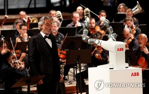(피사 AFP=연합뉴스) 맹인 테너 안드레아 보첼리가 12일 이탈리아 피사의 베르디 극장에서 로봇 '유미'가 지휘하는 루카 필하모닉 오케스트라에 맞춰 노래를 부르고 있다.