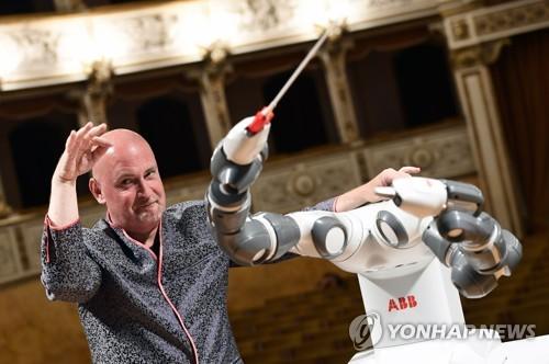 (피사 AFP=연합뉴스) 루카 필하모닉 오케스트라의 상임지휘자 안드레아 콜롬비니가 12일 이탈리아 피사 베르디극장에서 지휘하는 로봇 '유미'(Yumi)와 나란히 손동작을 취하고 있다.