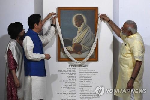 13인 인도 구자라트 주 아메다바드의 사바르마티 아슈람에서 나렌드라 모디(오른쪽) 인도 총리와 아베 신조 일본 총리 부부가 인도 독립의 아버지 마하트마 간디 초상화 앞에 끈을 걸고 있다.[AFP=연합뉴스]
