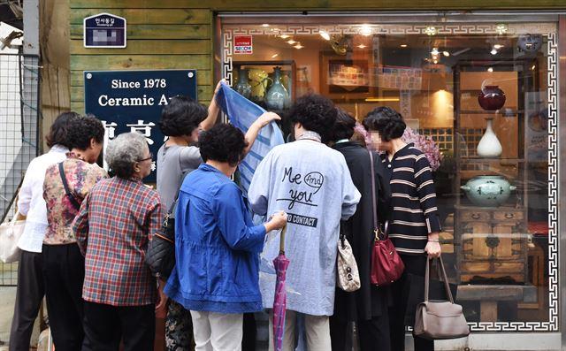 11일 인간문화재의 도예 작품이 진열된 인사동의 한 도예점 앞에서 중년 여성들이 점포에서 내 놓은 스카프를 고르고 있다.