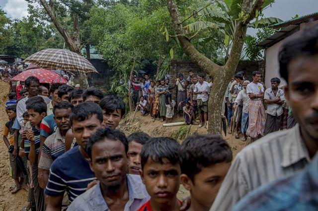 13일 방글라데시 쿠투팔롱 난민촌에 도착한 로힝야 난민들이 임시 대피소를 만들 재료를 보급받기 위해 줄을 서고 있다. 쿠투팔롱=AP 연합뉴스
