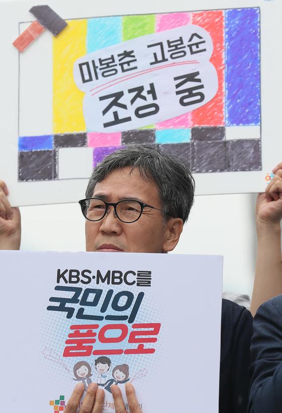 시민사회단체 회원이 6일 오후 서울 광화문광장에서 열린 공영방송 정상화를 위한 총파업 지지 기자회견에서 손팻말을 들고 있다. [연합뉴스]