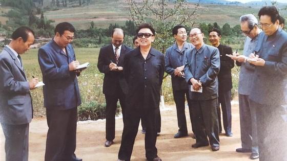 김용순 대남비서(오른쪽 끝)가 1999년 9월 자강도 낭림군에 새로 건설된 문화주택을 현지지도하는 김정일 국방위원장의 지시를 메모하고 있다. [사진집 영도자와 인민]