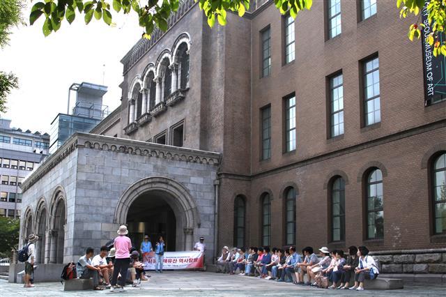 그랜드투어 참석자들이 서울시립미술관 현관에 편안하게 걸터 앉아 정동과 덕수궁 이야기를 듣고 있다. 이곳은 독일공사관·경성지방법원·대법원을 거쳐 시립미술관으로 자리잡았다.