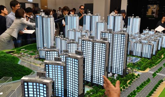 고분양가를 억제하기 위한 정책이 만들어낸 아파트 수요로 청약시장이 들끓고 있다. 서울 송파구 문정동 래미안갤러리에 마련된 '래미안 강남포레스트' 모델하우스를 찾은 시민들이 단지 모형을 살펴보고 있다.  /연합뉴스