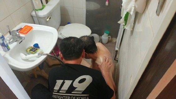 라문석 대장이 중증 지체 장애인 백모씨의 집을 찾아가 목욕을 시키고 있는 모습. [사진 본인 제공]